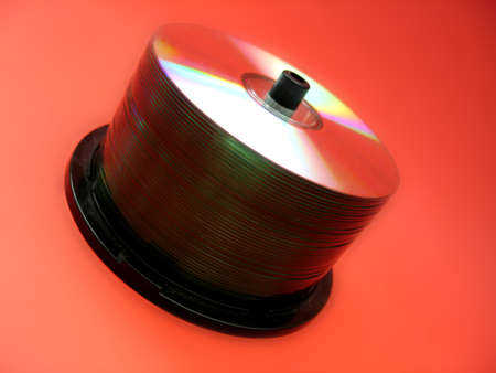 A spindle full of blank CDs on a red background.