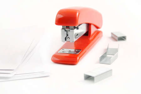 office stapler: Red stapler with staples and assorted papers