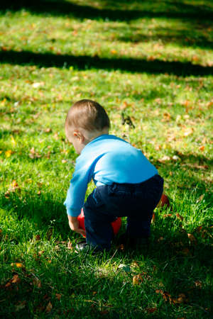 Adorable little boy squatting down to pick up his ball