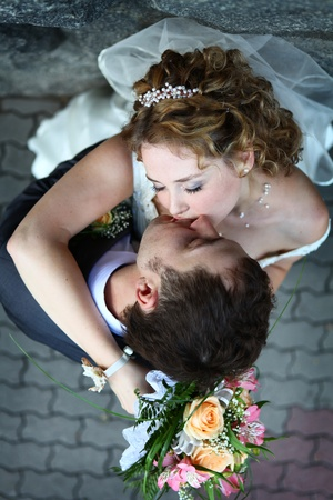 Bride and groom kissing near stone wall