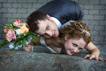 Young beautiful bride and groom near stone wall photo