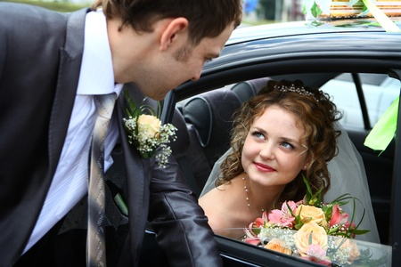 Bride in car and groom looking on her Stock Photo