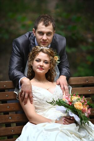Bride sitting on the bench and groom in park photo