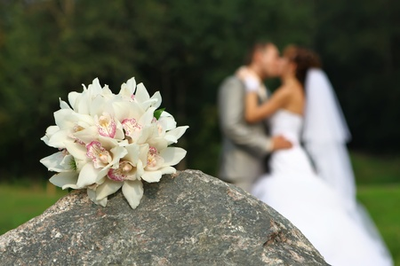Bouquet on stone and bride and groom kissing Stock Photo