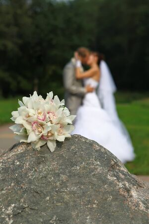 Bouquet on stone and bride and groom kissing photo