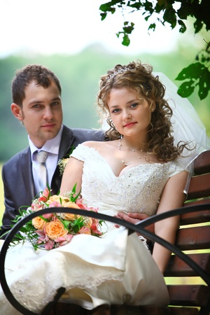 Bride and groom sitting on the bench in park photo
