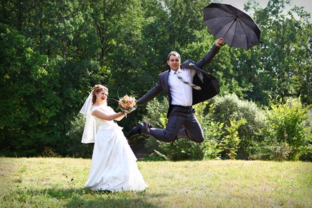 Bride and groom flying on umbrella in summer park photo