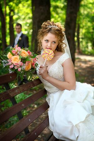 lollypop: Groom and bride on bench with lollypop Stock Photo