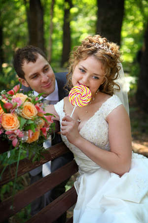 Groom and bride on bench with lollypop Stock Photo