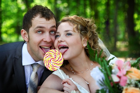 lollypop: Bride and groom in park eating lollypop together Stock Photo