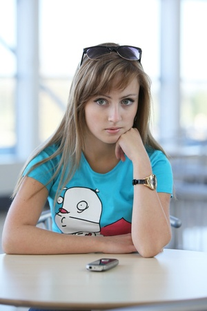 Young beautiful woman sitting at the table in cafe witn a phone and waiting to somebody photo