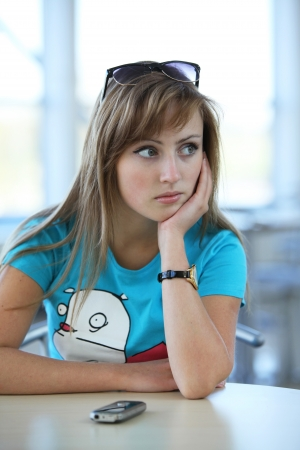 Young beautiful woman sitting at the table in cafe witn a phone and waiting to somebody