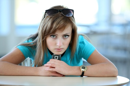 Young woman sitting at the table in cafe with a phone Stock Photo