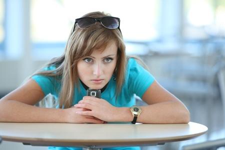 젊은 아름 다운 여자는 카페 witn의 휴대 전화에 테이블에 앉아 누군가를 기다리는