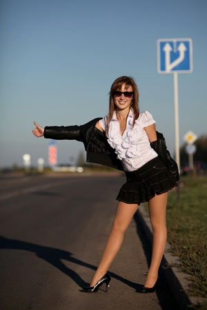 runaway: Young woman catching taxi on the road Stock Photo