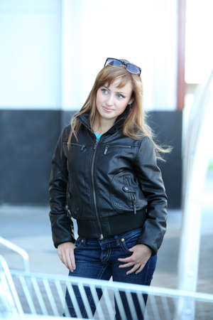 Young fashioned woman in black jacket and jeans