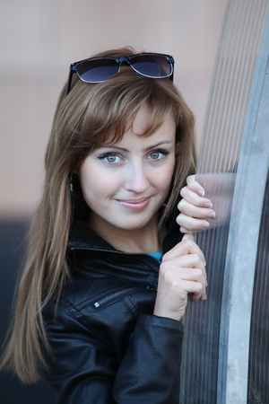 Young beautiful smiling woman in black jacket and glasses photo
