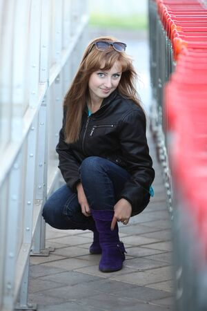 Young fashioned woman in violet boots in supermarket photo