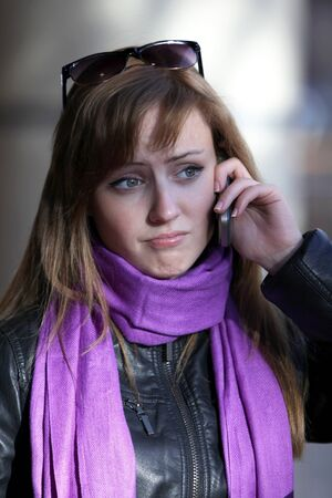 Upset young beautiful woman witn mobile phone photo