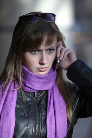Upset young beautiful woman witn mobile phone photo
