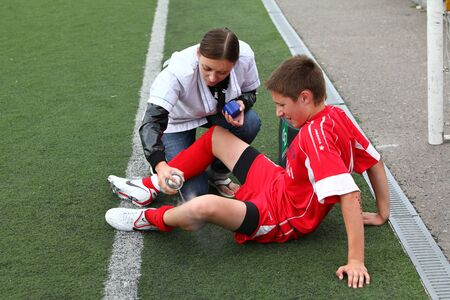 BELGOROD, RUSSIA - AUGUST 20: Unidentified nurse helps to unidentified boy on football field on August, 20 2010 in Belgorod, Russia. The final of Chernozemje superiority, team of 1996 year of birth.  Stock Photo - 11556165