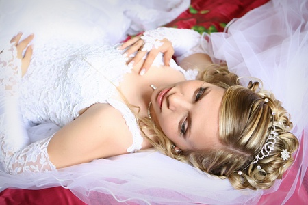 Young beautiful bride laying on the bed photo