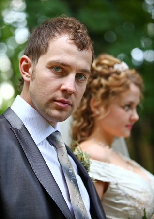 Groom in grey suite and bride behind him