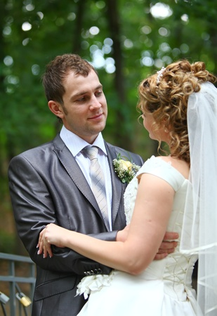Groom and bride embracing in summer forest