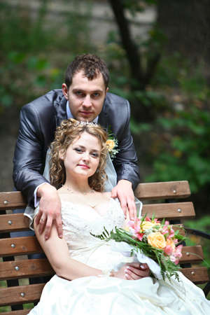 Groom and bride embracingon the bench in summer forest photo
