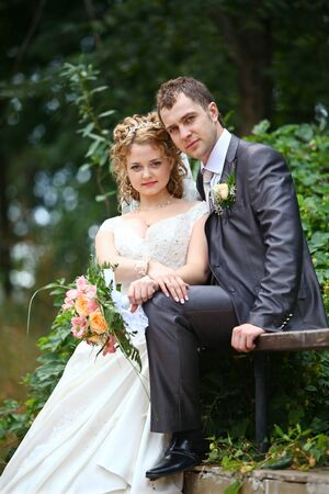 Groom and bride embracing in summer forest photo