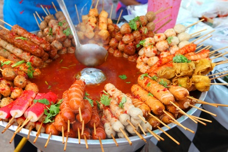 Meat balls and sausages on sticks in a bowl with sauce on Phuket market, Thailand