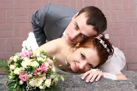 Wedding couple near stone wall