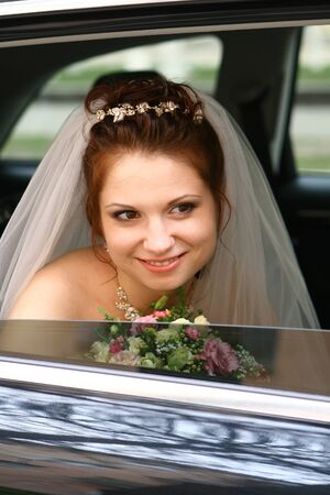 Bride with flowers in the car photo