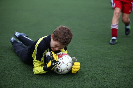 BELGOROD, RUSSIA - JULY 4  Unidentified boy plays football as goalkeeper July, 4 2010 in Belgorod, Russia  The final of Chernozemje superiority, Football kinder team of 1998 year of birth   Stock Photo - 13538078
