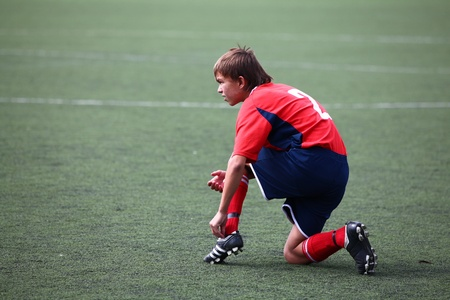 BELGOROD, RUSSIA - AUGUST 20  Unidentified boy fastening laces on boot on August, 20 2010 in Belgorod, Russia  The final of Chernozemje superiority, team of 1996 year of birth