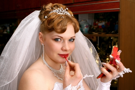 Beautiful bride looking in the small mirror photo