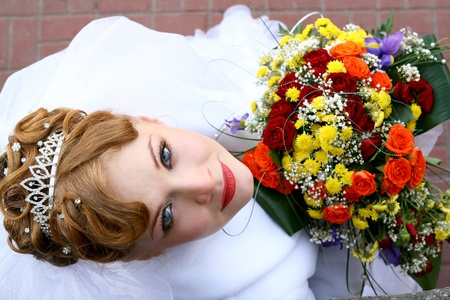 bridal hair: Bride looking up with a bouquet