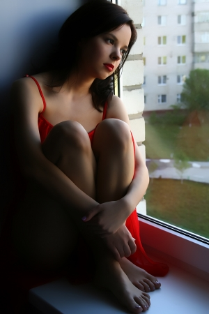 Young lady in red dress looking in the window photo