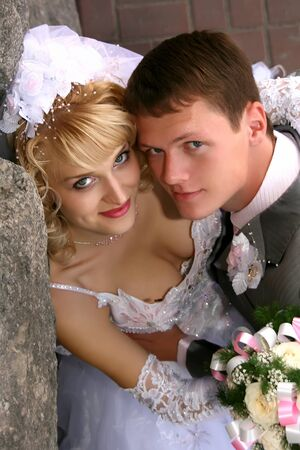 Wedding couple near stone wall photo