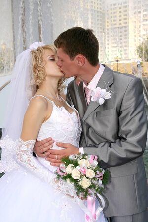 Bride and groom kissing near fountain