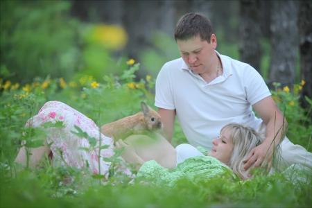 토끼와 숲에서 임신 한 여자와 그녀의 남편 스톡 콘텐츠