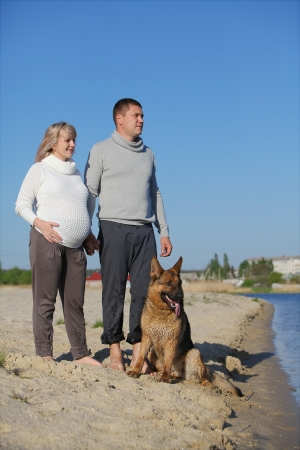 Pregnant woman and man with sheep-dog Stock Photo