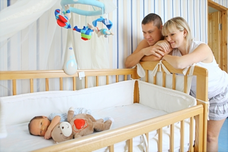 Happy parents near baby s bed photo