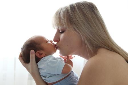 2 months: Mother kissing newborn