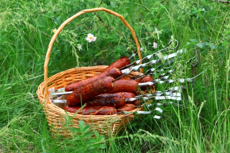 Roast sausages in the basket in the grass