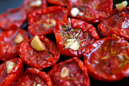 A plate with dried tomatoes with garlic and rozemary photo