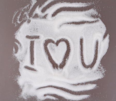 declaration of love: Declaration of love written on the sugar scattered on a kitchen table Stock Photo