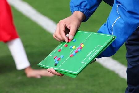 jugando futbol: Entrenador de fútbol da instrucciones a los jugadores en el escritorio Foto de archivo