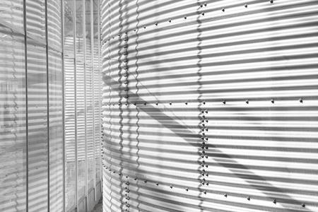 Metal wall of tank inside industrial building