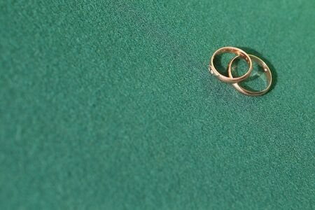 Background with two golden wedding rings on green cloth Stock Photo